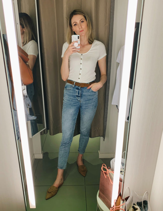 2019 Black Friday and Cyber Monday Deals | Black Friday Sales and Deals by popular California life and style blog, Tea Cups and Tulips: image of a woman standing in a dressing room and wearing a white t-shirt and jeans.